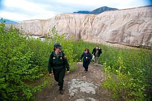 a park ranger leads two visitors up a trail