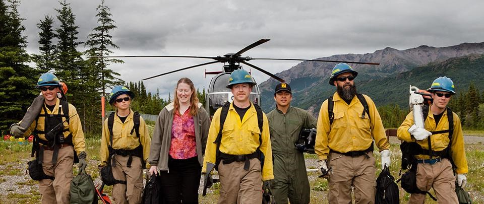 the western area fire crew walks in front of a helicopter