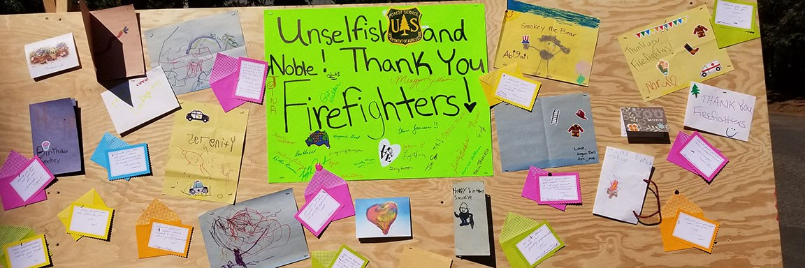 A fire camp board filled with posters and thank you cards.