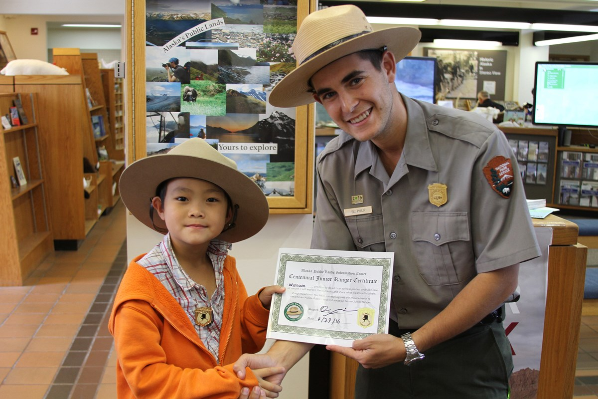 A ranger presents a child with a Jr Ranger certificate and badge