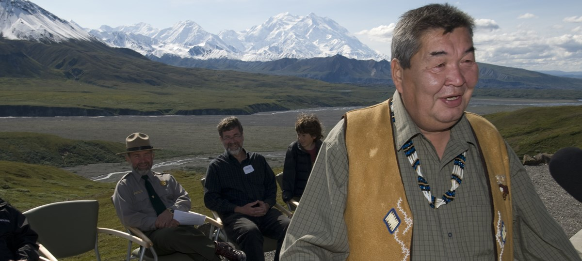Chief Mitch Demientieff speaks at a podium in Denali National Park and Preserve with park staff and mountains in the background