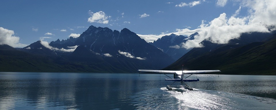 A float plane on a high alpine lake taxis for takeoff.