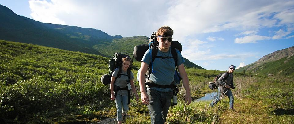 three hikers walk with packs through Denali National Park