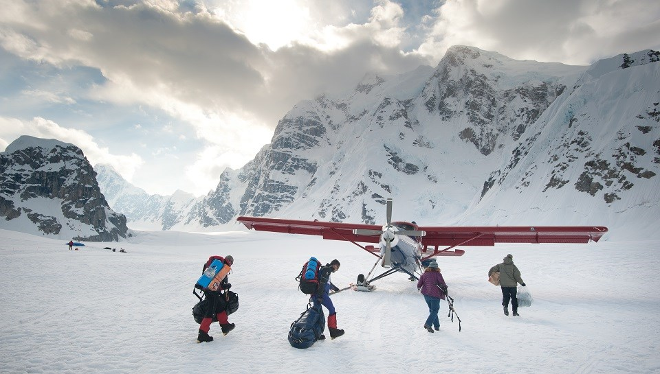 Four hikers on a snowy mountain walk with gear to a plane on skis.