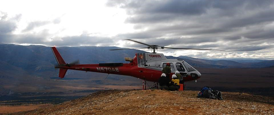 a crew wearing hardhats loads a helicopter on a hill