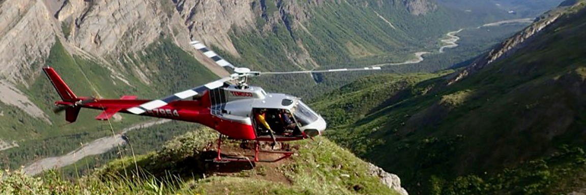 The red and white 970TH helicopter sits momentarily idle on an outcropping overlooking a valley.