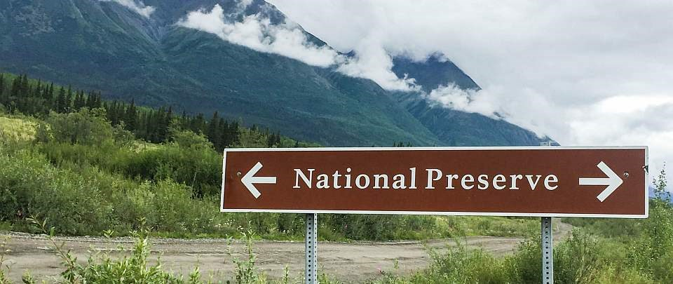a sign that says national preserve in front of mountains