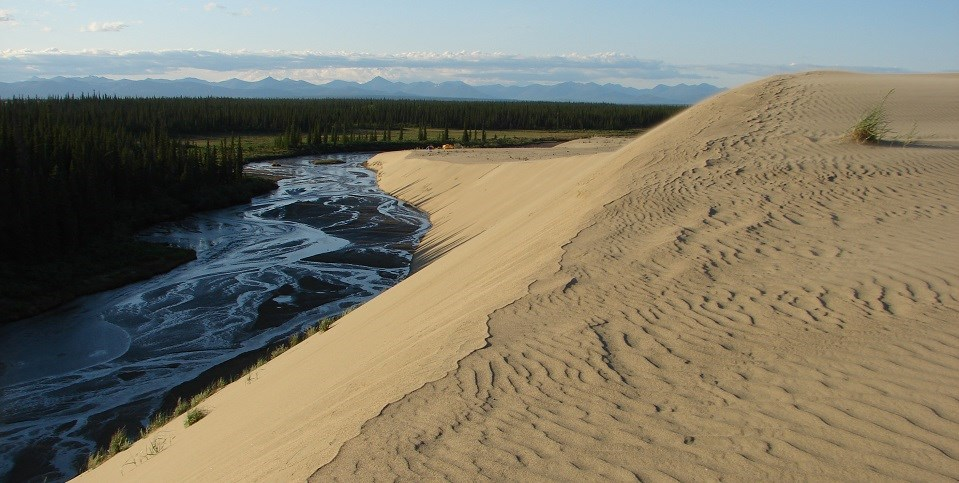 Sand dunes display wind ripples and overlook a river valley.