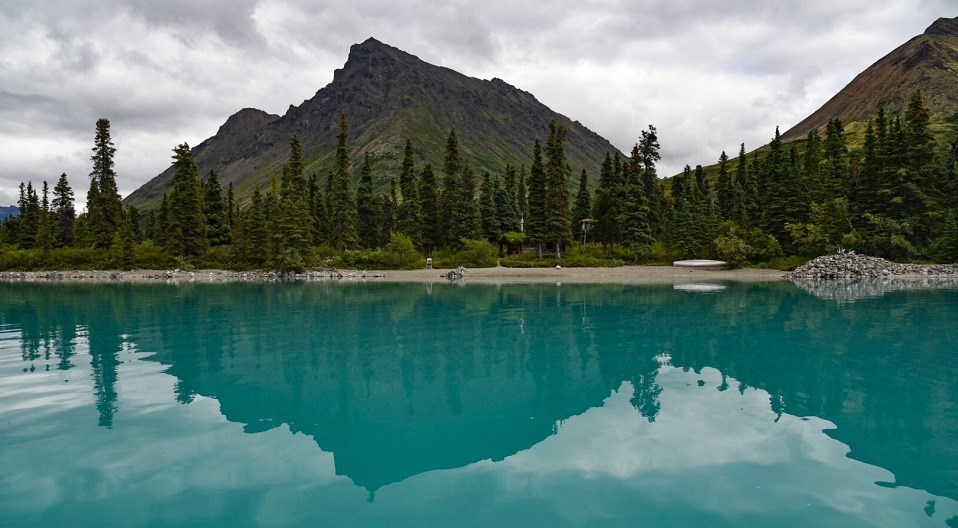 Green and brown mountains, spruce trees, a wooden cabin and a metal canoe reflect in a turquoise lake.