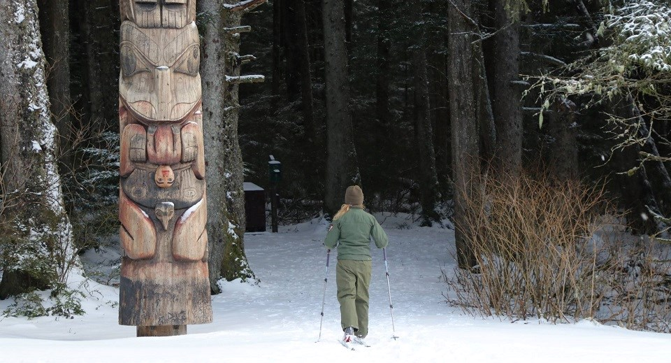 A female park ranger skis next to a totem pole on a snowy trail into the woods