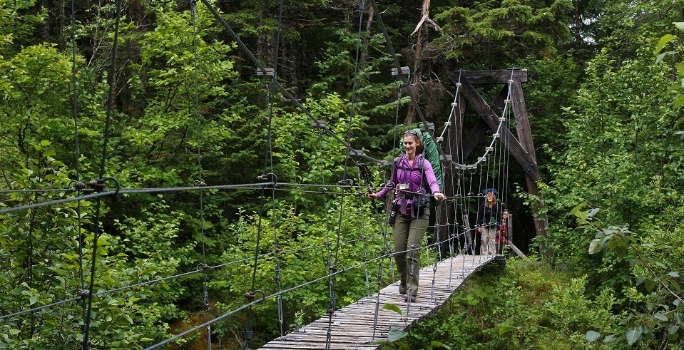 A woman with a backpack walks across a suspension bridge in a wooded area