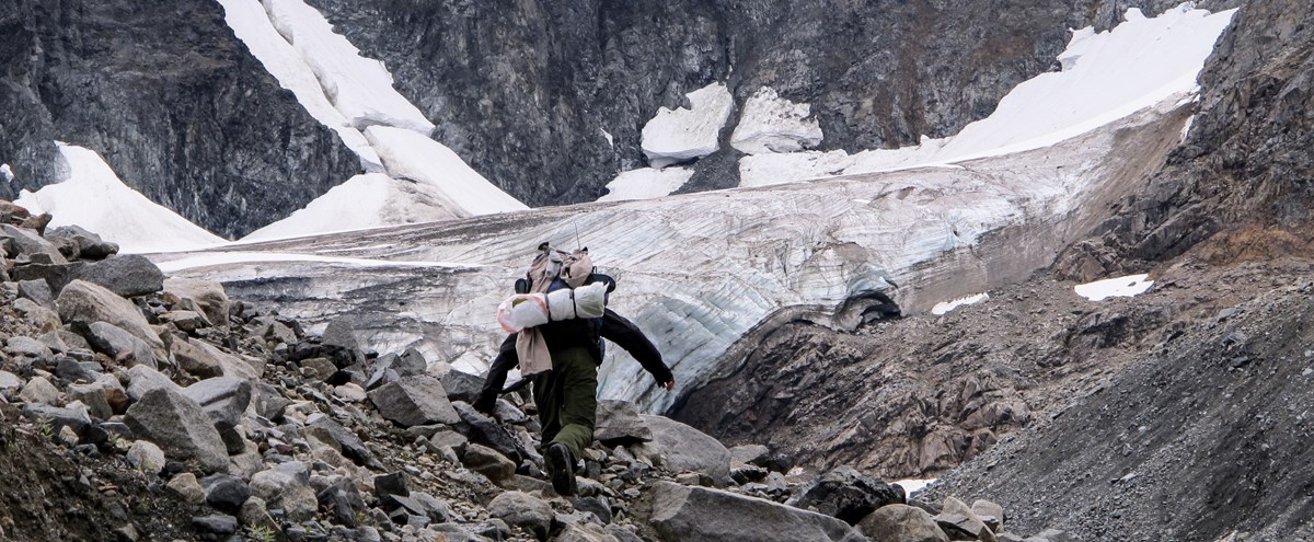 a person with a large backpack walks up a rocky ravine in front of a small glacier