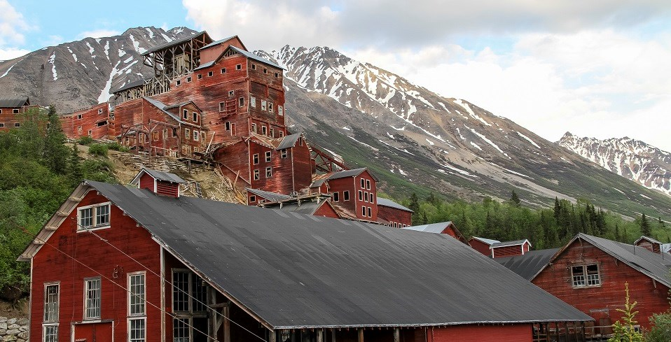 A red wooden building sits on a mountainside