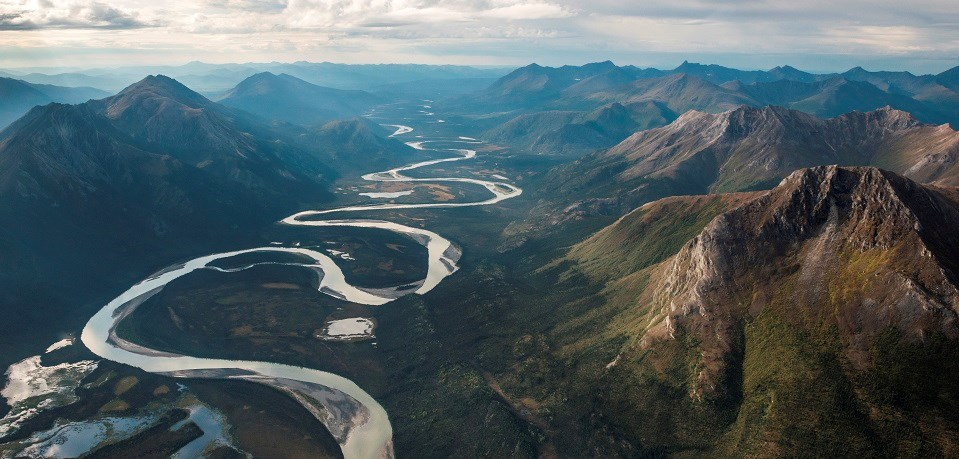"a river winds through mountains making many ""S"" curves"