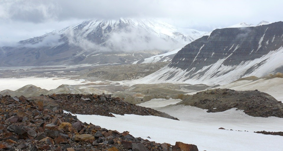 Red rocks and a glacier are backdropped by snowy mountains