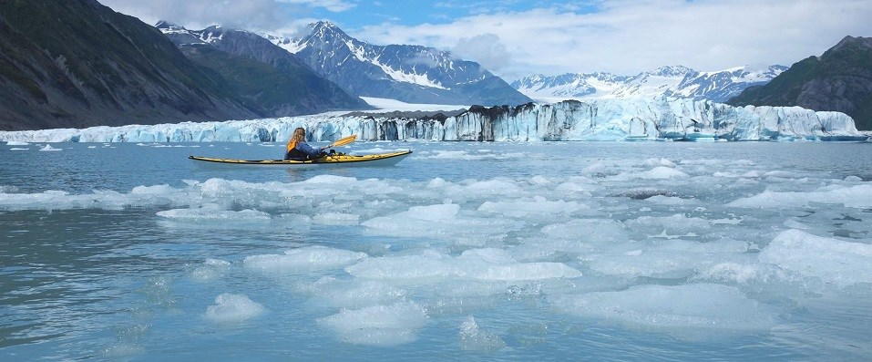 A kayaker paddles through ice in front of a glacier.