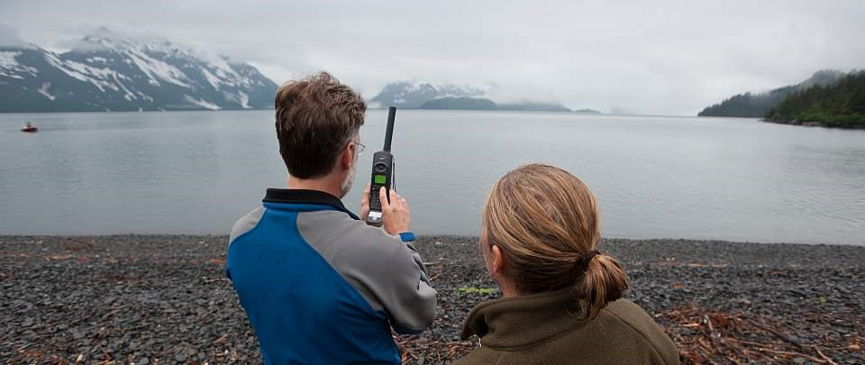 a man uses a satellite phone next to a women on a foggy beach