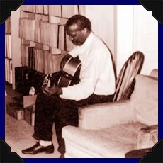 Skip James holding a guitar