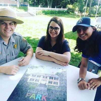 A ranger and two volunteers with a Find Your Park puzzle on the Longfellow front lawn