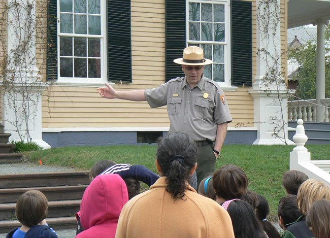 Ranger talking to group of children in front of Longfellow House