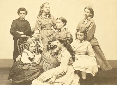 Group portrait of woman seated with six girls and one boy seated and standing around her