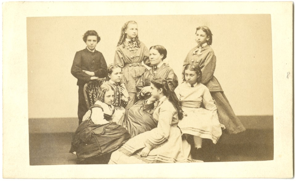 Studio portrait of six girls and one boy group around woman seated in center