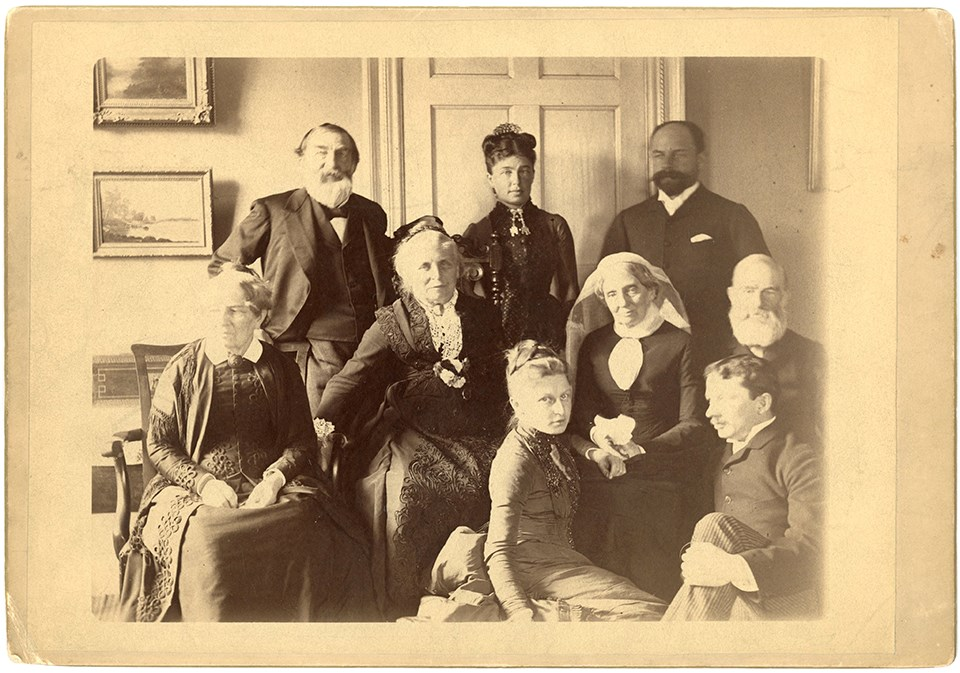 Group portrait of family seated and standing in interior of home