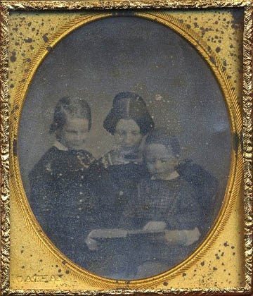 Daguerreotype of woman reading to two boys in oval case opening.