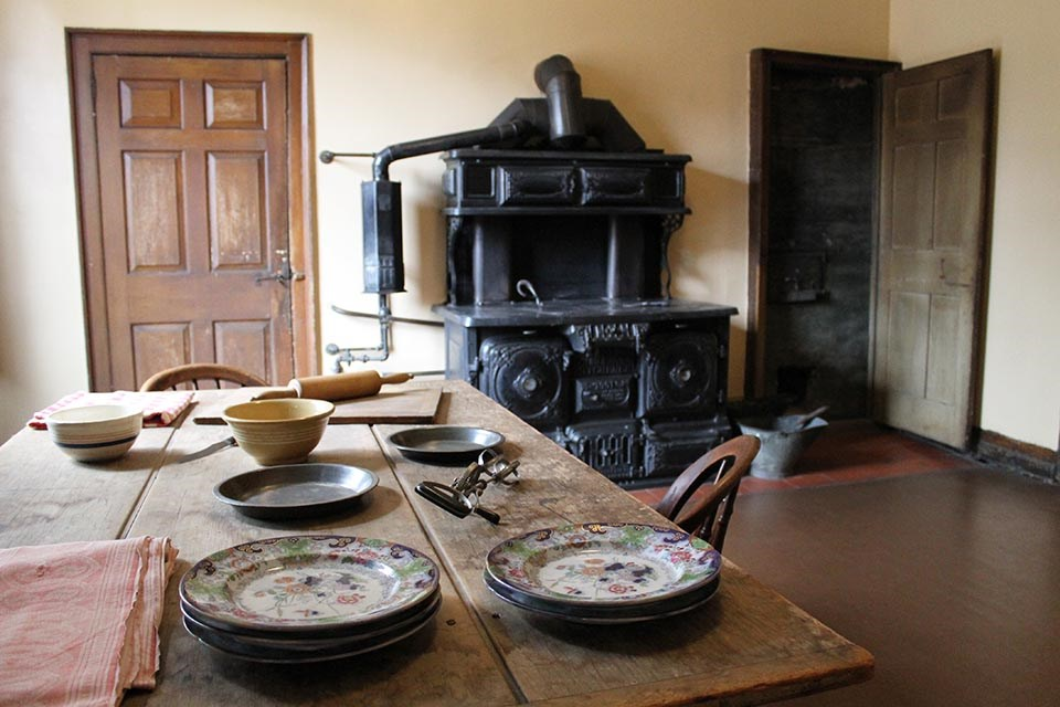 View of kitchen with large coal stove in background, table with plates and kitchen tools in foreground