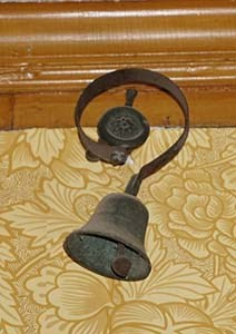 Bell hanging on curved metal bracket