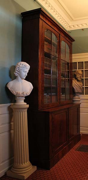 Floor to ceiling bookcase flanked by a marble bust of angel with flowers and plaster bust of Henry Longfellow