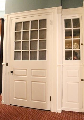 Wide, white paneled door with screen insert, narrow glass-fronted china cabinet