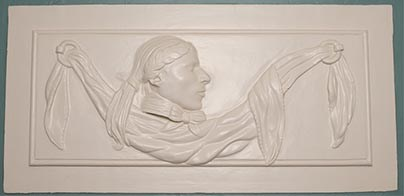 White-painted relief of man in profile with laurel wreath, bow at neck, and drapery across panel