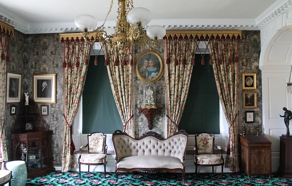 Interior of room with floral wallpaper, drapes, carpet, and upholstery, sofa and two chairs along wall with two windows