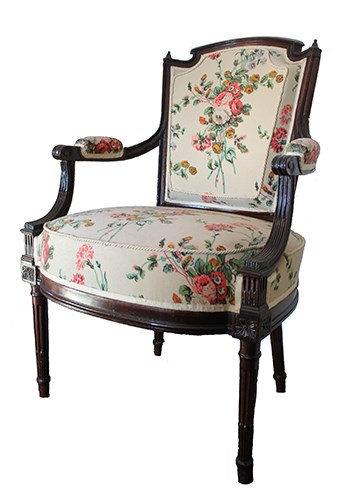 Armchair with seat and back upholstered in floral pattern on tan background.