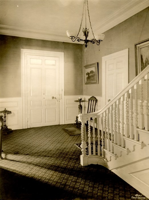 Black and white photograph of a hallway with stairs in the foreground and a large door on the opposite wall.
