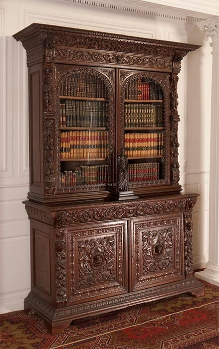 Tall, ornately carved bookcase. Upper case with arched glass windows showing four shelves of books. Lower case with ornately carved wooden doors.