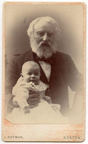 Bearded man in suit seated, holding baby in long white dress on his lap