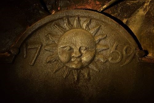 Iron fireback depicting a sun with a face flanked by the date 1759