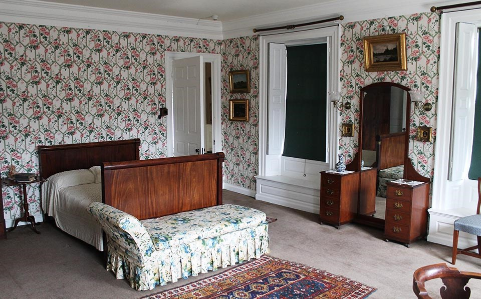 Interior of bedroom with sleigh bed and chaise at center