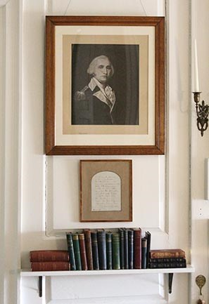 Framed print of portrait of Washington hanging above framed manuscript page and shelf of books