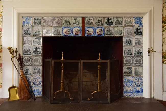 Fireplace with andirons and screen surrounded by multicolored tiles