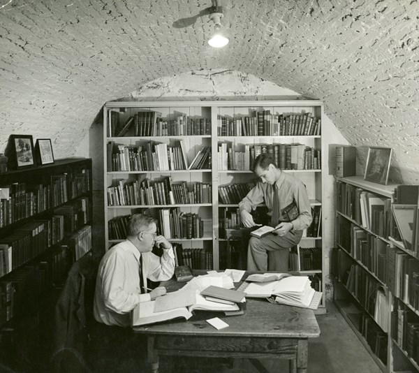 Two men surrounded by books in the basement archives, circa 1935