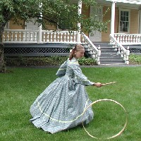 A volunteer in period costume plays a 19th century lawn game.