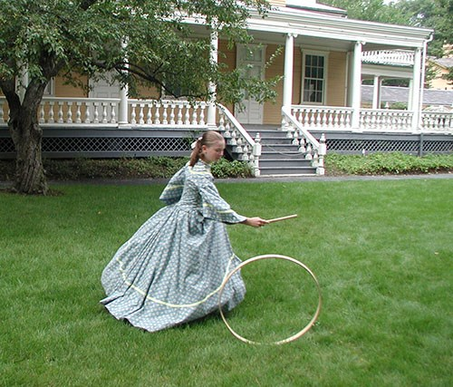 Girl in blue Victorian dress running with hoop and stick