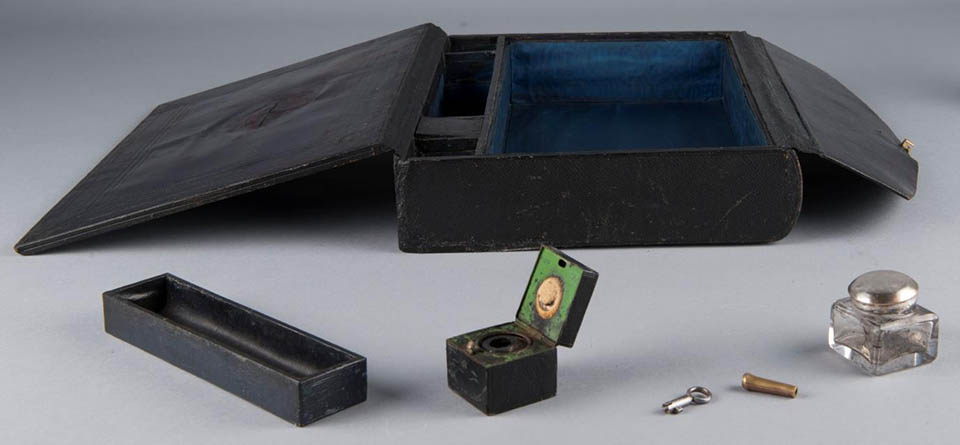 Black box with two top flaps open revealing blue interior, small black tray, two inkwells, small key, and metal ferrule on table in front of case