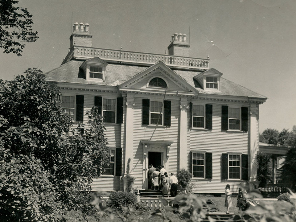 Black and white photo of visitors entering Longfellow House through front door