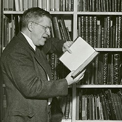 Man standing in front of bookshelf with book in hands