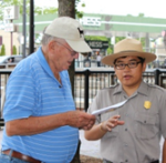 A young male ranger talking to a visitor while holding a piece of paper
