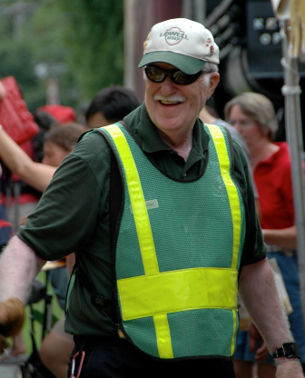 A male volunteer wearing a reflective vest crossing the street during the Lowell Folk Festival